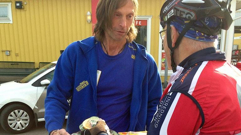 Ola-Conny välkomnar cyklisterna. Foto: Sveriges Radio