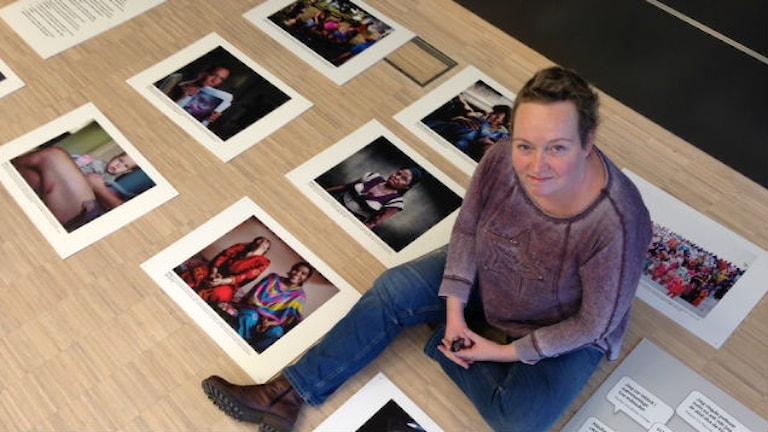 Annelie Hagberg från Varbergs kvinnojour bland bilder som ska bli utställningen Dödsorsak: Kvinna. Foto: Sveriges Radio