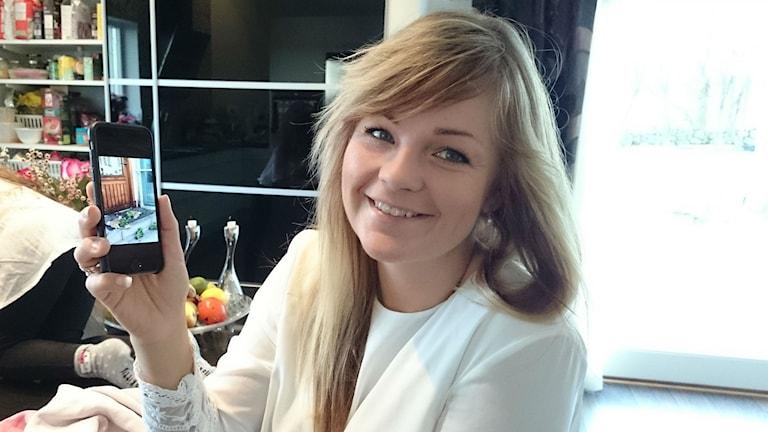 Pernilla Acar Boström visar upp en bild av den sönderskjutna myntan som hon tror kommer från Esthers. Foto: Jonna Burén / Sveriges Radio