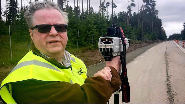 Stefan Kaleby från trafiksäkerhetsföreningen NTF mäter hastigheterna på bilarna som far förbi ett vägarbete på väg 26 norr om Hylte.