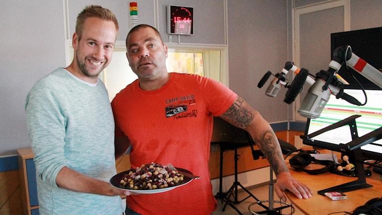 Programledare Mattias Persson står bredvid gästen Patrik Olsson och håller i en tallrik med bönor.