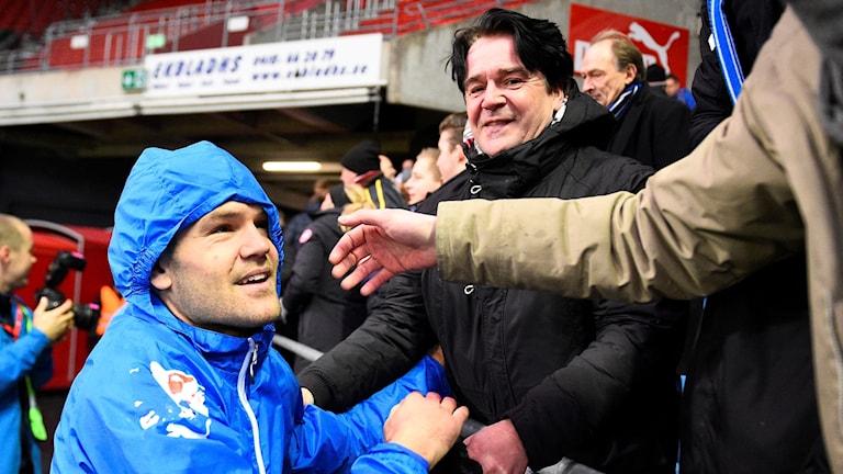 Ivo Pekalski, iklädd blå jacka med huva, står framför några personer i publiken, som gratulerar honom efter att HBK lyckats avancera till Allsvenskan efter kvalet mot Helsingborg.