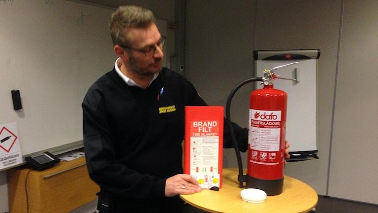 Brandinspektören Börje Knutsson i Halmstad visar vad som bör finnas hemma när det gäller brandskydd. Foto: Andreas Svensson/Sveriges radio