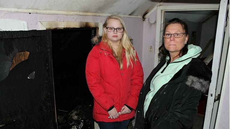 Sandra och Susanne Fors bredvid ingång till den helt urbrända vinden. Foto: Henrik Martinell / Sveriges Radio