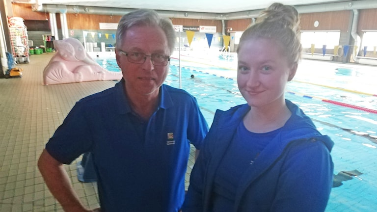 En man och en kvinna står i en simhall. De är klädda i likadana blåa kläder och tittar in i kameran.