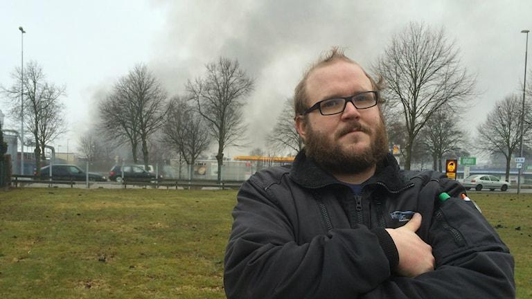 Andreas Klintgren, i bakgrunden syns rök från hans arbetsplats som brunnit upp.