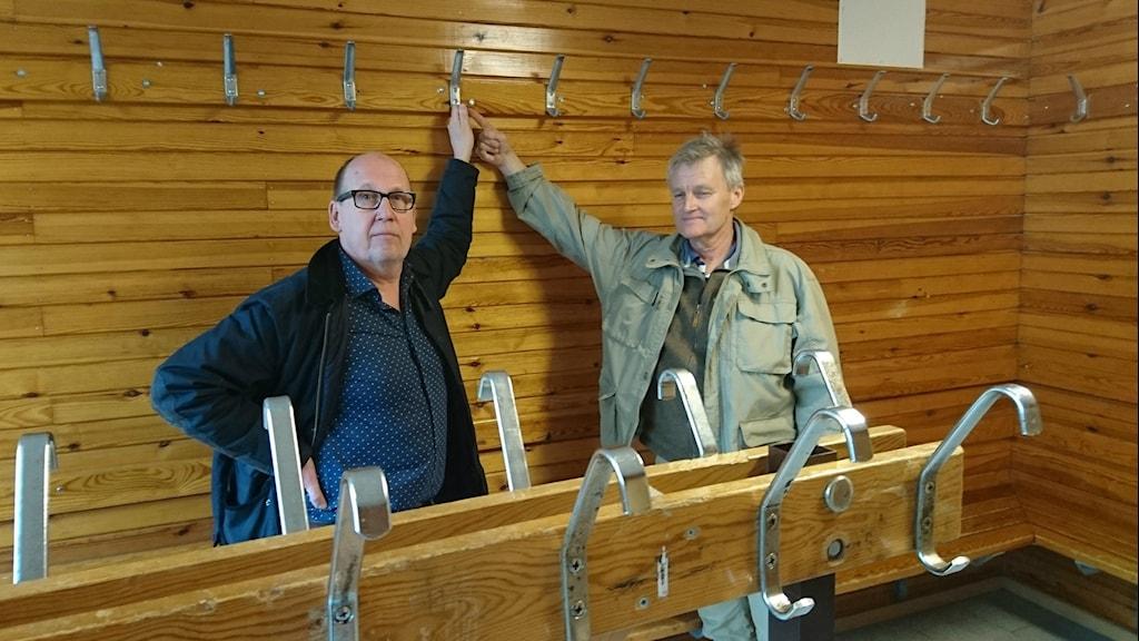 Per Hallström, ordförande i Alets IK, och Stefan Bokström, fd målvakt i samma lag, håller i kroken där Janne Andersson brukade hänga sina matchkläder.