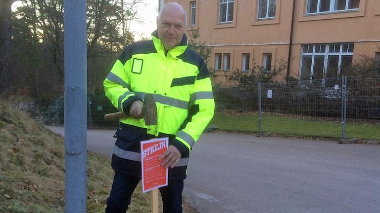 Strejkvakt ombudsman Stefan Bergman från Byggnads slår ner strejkskylten vid Spenshults gamla sjukhus. Foto: Andreas Svensson/Sveriges Radio.