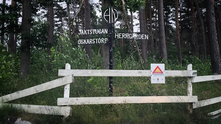 Ett vitt trästaket och bakom det en skylt som pekar mot herrgården till höger, och jaktstugan och oskarstorp till vänster.