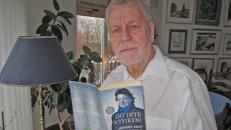 Björn Hellberg sitter med en bok i handen.