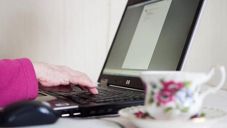 Kvinna sitter framför dator.