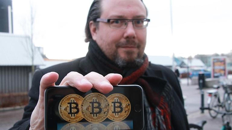 Adjunkt Mattias Wecksten på Högskolan Halmstad håller upp mobiltelefon med bitcoins