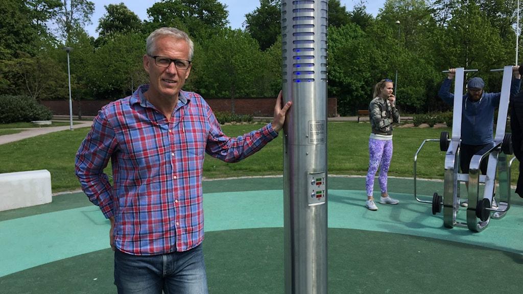 Urban Johnson bredvid stolpen vars teknik styr träningsredskapen i det intelligenta utegymmet i Halmstad. Foto: Therése Alhult/Sveriges Radio.