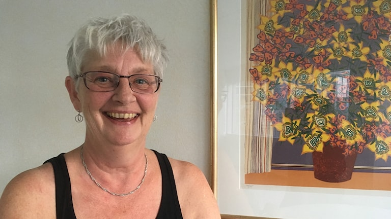 Carina Johansson står leendes bredvid en färgglad tavla.