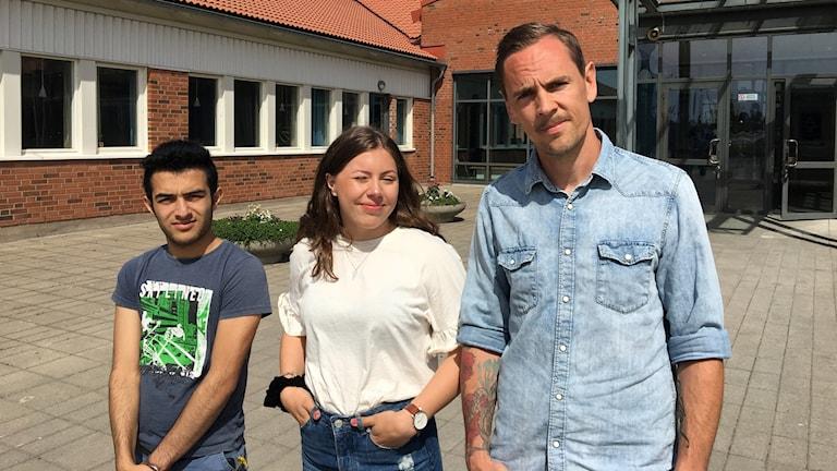Tre personer står framför en tegelbyggnad och ler mot kameran.