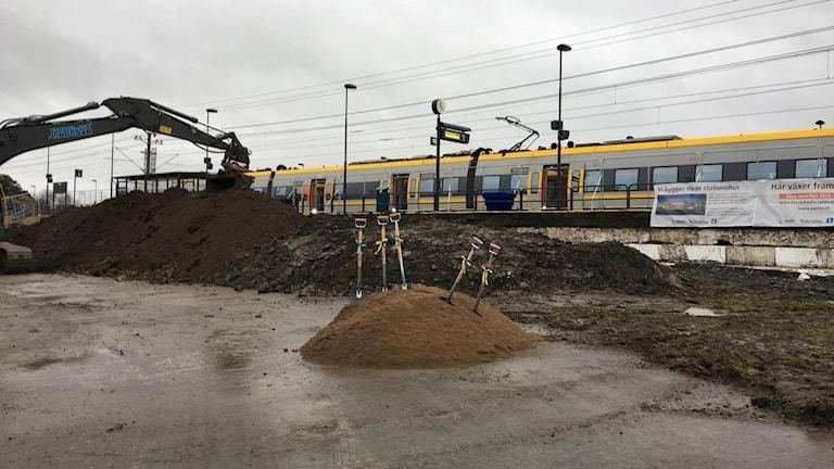 Grävskopa tar jord framför tåg på stationsområdet