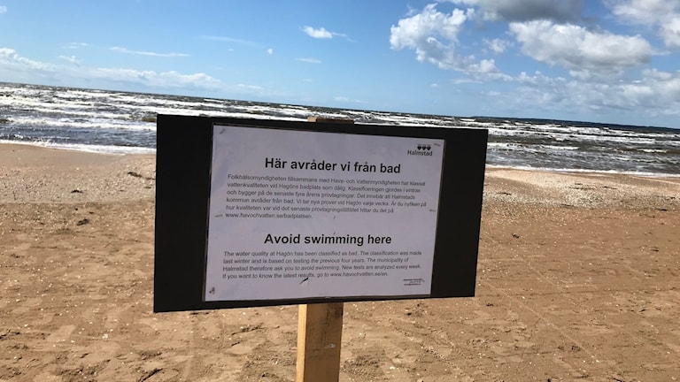 En skylt  med badavrådan framför havet.