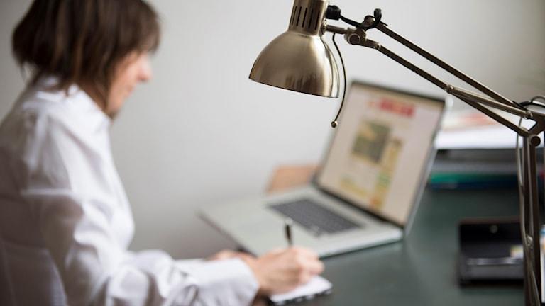 kvinna sitter framför en dator och jobbar.