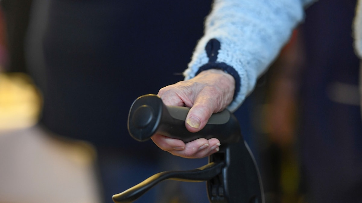 närbild på hand som håller på handtag till rullator