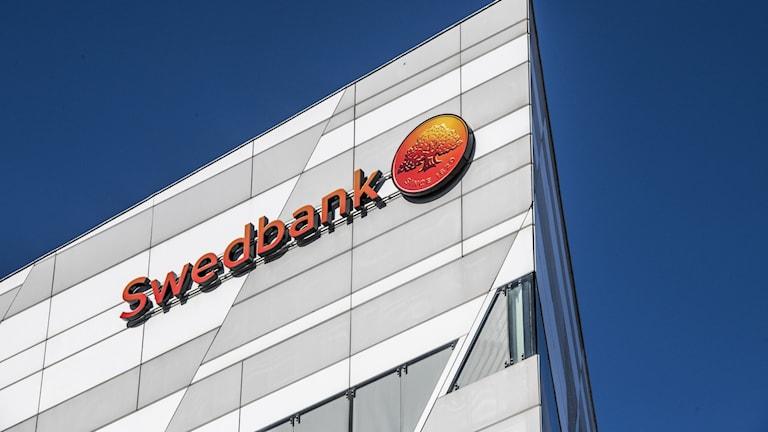 Bild på ett av Swedbanks kontor tagen underifrån med blå himmel som bakgrund.