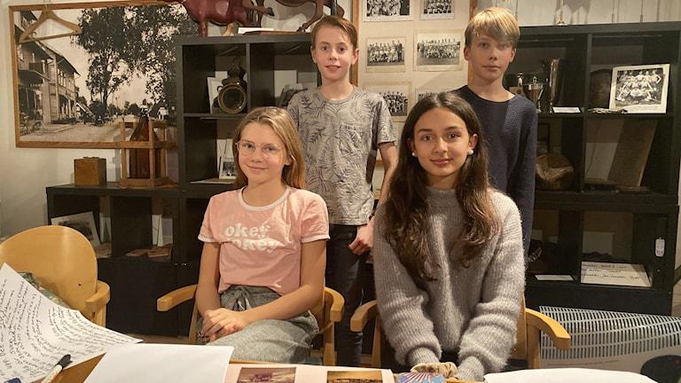 Hanna och Ariella sitter och Vidar och Love står bakom, i förgrunden ser man bordet där det finns massor med papper och foton.