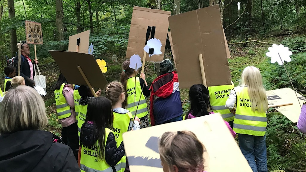 Barn med reflexvästar går i en skog. De håller i kartongplakat med texter på och protesterar.