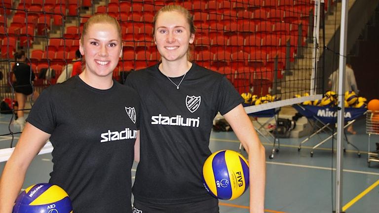 Stina Rix och Martina Svensson står framför ett volleybollnät med volleybollar under armarna.