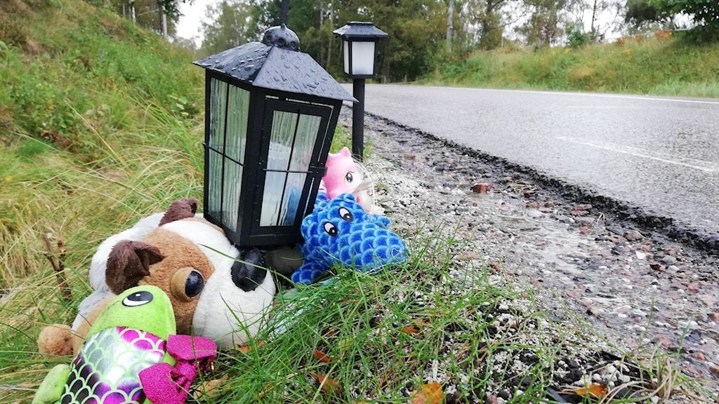 Tre gosedjur och en lykta ligger vid olycksplatsen intill vägen.