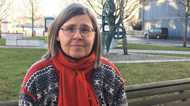 Porträtt på kvinna, Sara Ekström, i utemiljö bärandes röd halsduk och mönstrad tjocktröja.