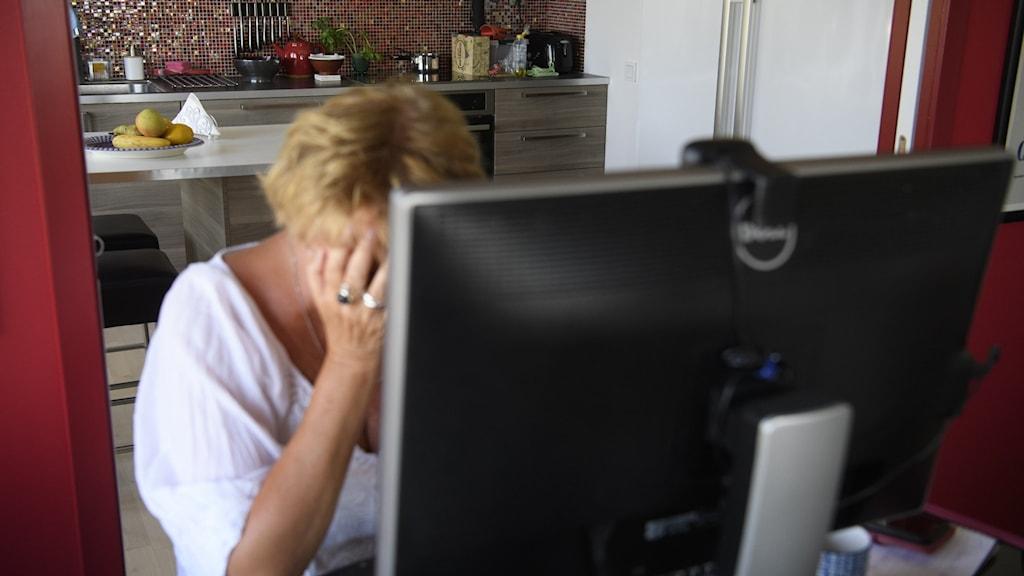 En kvinna sitter framför en dator och håller händerna för ansiktet.