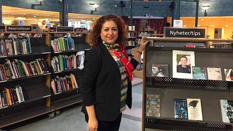 Susan Pour står bland bokhyllor i ett bibliotek.