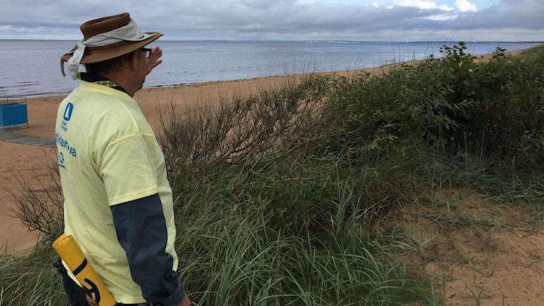 Anders Agerström blickar ut mot stranden och förklarar att Strandens dag sker oavsett väder.