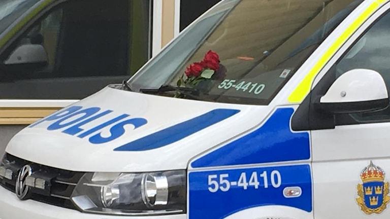 det ligger fyra röda rosor på en polisbil.