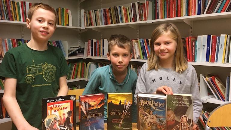 Vidar Sandström, Love Mogren och Hanna Jelic håller upp böcker de läser i skolans bibliotek.