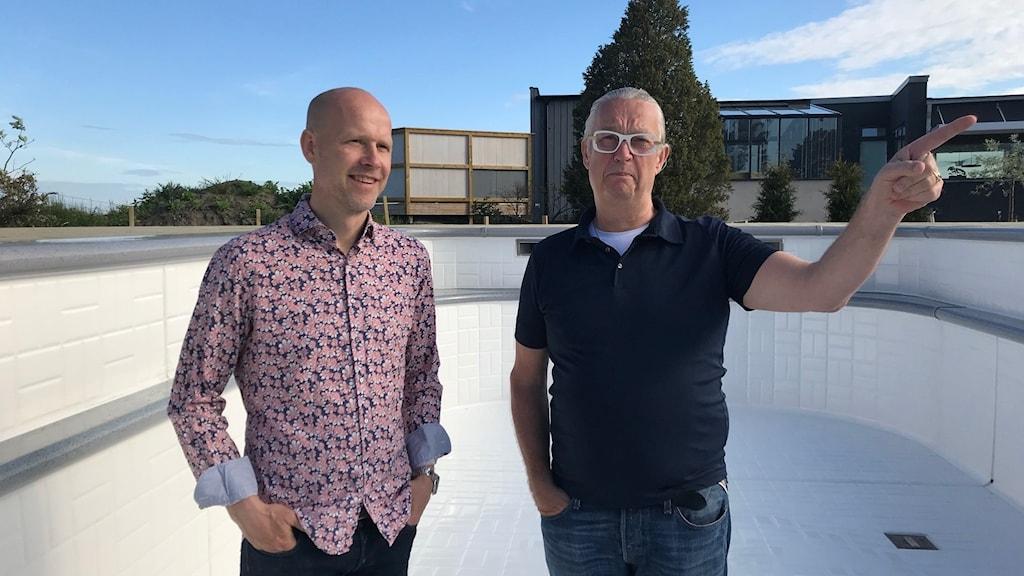Två män står i en tom pool som håller på att byggas.