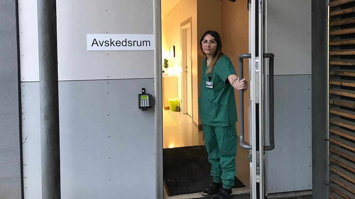 Obduktionstekniker öppnar dörren till avskedsrummet vid bårhuset.