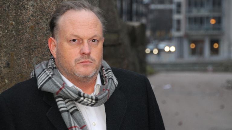 Mathias Josse, iklädd svart jacka och halsduk, står utomhus.