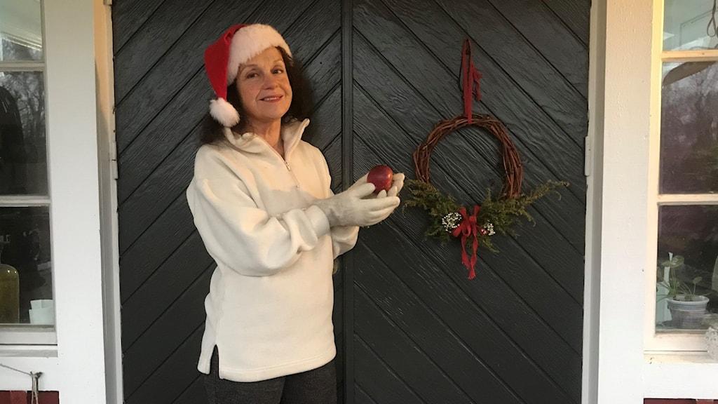 Ann Jornéus står utanför ytterdörren och önskar en fröjdefull jul!
