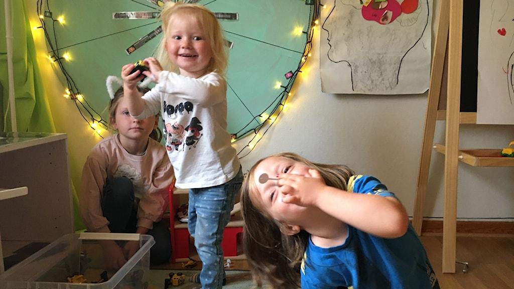 Tre förskolebarn leker och tittar in i kameran.