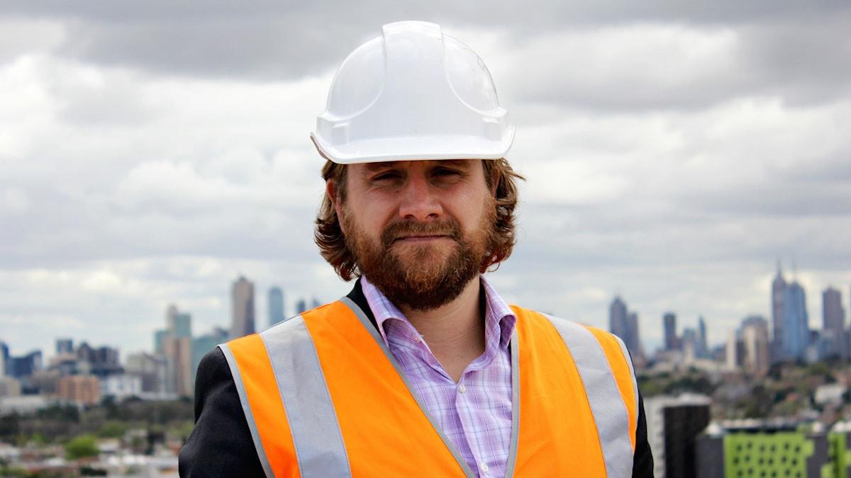 En man i byggställ står med Melbourne i bakgrunden.