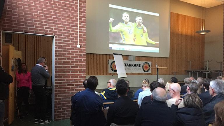 Janne Andersson dricker en kopp kaffe innan han ger sig upp på scen inför en fullsatt aula på Brunnsåkerskolan.