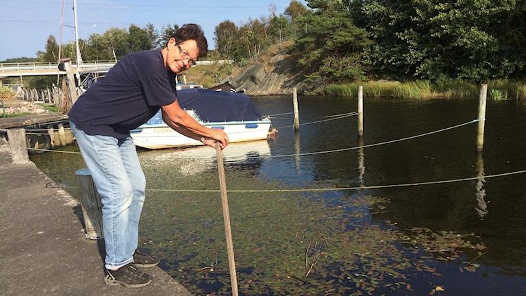 Birgitta står lutad över en båtshake som är nedstucken i ån. Hon har blå jeans och en mörkblå t-shirt. Det är soligt ute.