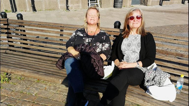 Två kvinnor sitter på en parkbänk och solar.