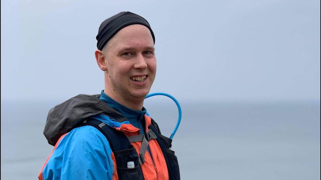 En man i träningskläder tittar åt sidan in i kameran och ler.