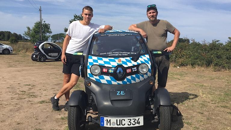 Två män vid en liten elbil.