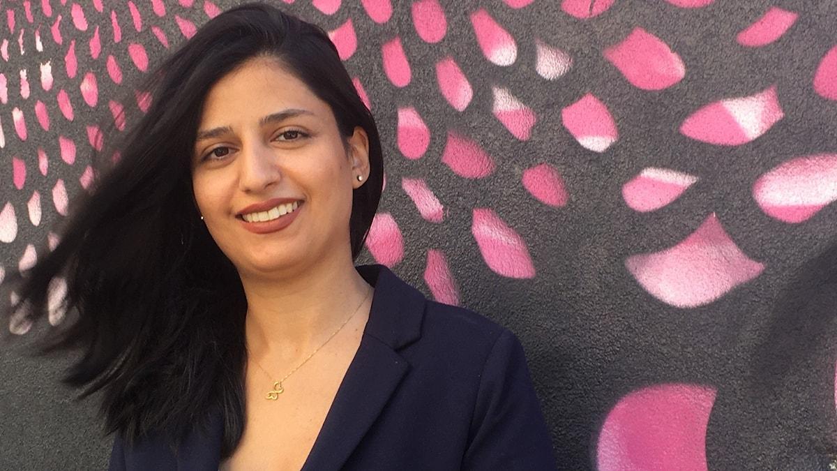 Porträtt framifrån på en leendes kvinna i svart kavaj och svart flygande hår, i bakgrunden syns en lila, vit och svart muralmålning.