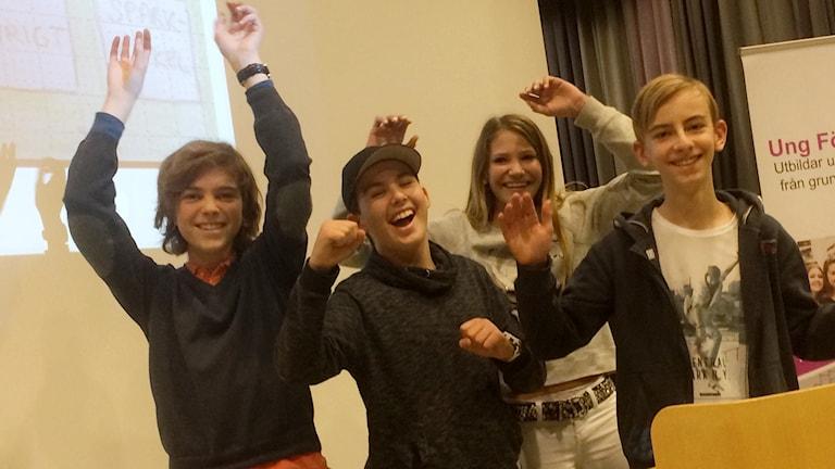 De fyra eleverna visar glädje genom att slå händerna ut i luften. I bakgrunden syns lite av en bildskärm där en bit av den föreslagna appen syns.