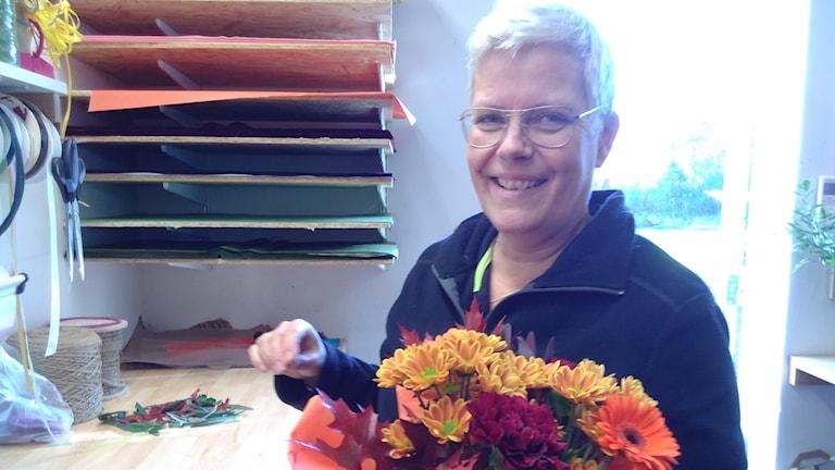 Mia Knudsen florist blomsterboden skottorp i blå fleectröja och med bukett blommor i handen.