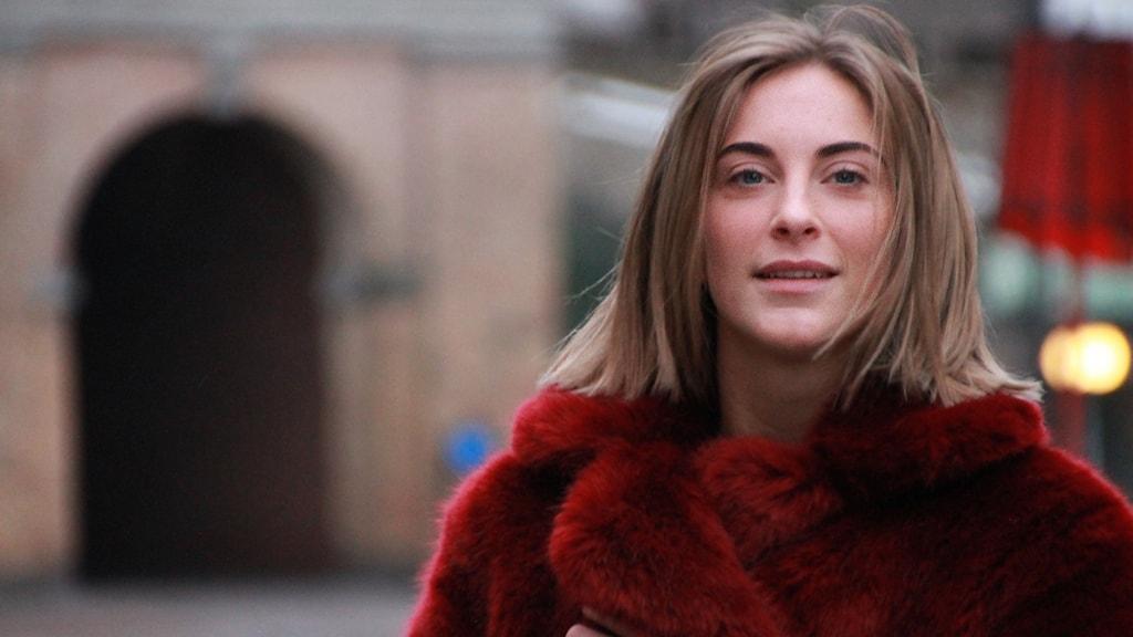 Porträttbild på en kvinna framför Norre port i Halmstad. Hon har på sig en röd, fluffig jacka och tittar in i kameran.