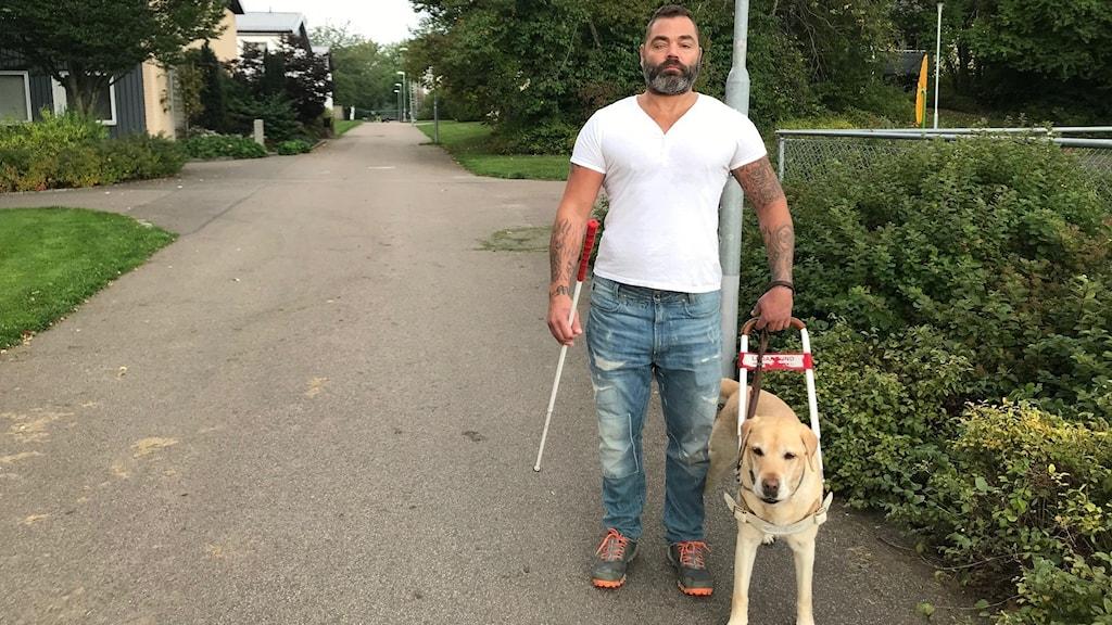 Man med ledarhund och vit käpp på gångväg